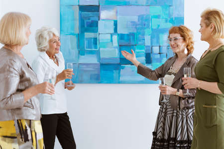 Four smiling and elegant women with champagne on opening Stock Photo