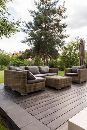 Wooden terrace at the backyard with couch, armchair and coffee table