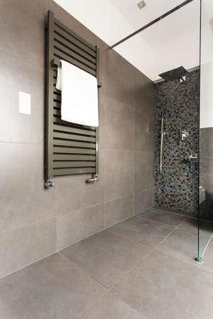Donkere moderne badkamer met grijze tegels, glazen douchecabine en radiator Stockfoto