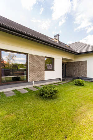 Modern detached house exterior with panoramic window in well-kept garden