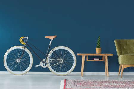 Elegante bicicleta y muebles vintage en el interior moderno Foto de archivo