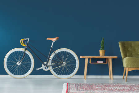 Stylish bike and vintage furniture in modern interior Stok Fotoğraf