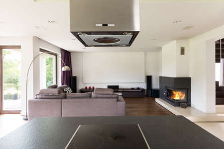 View from the kitchen countertop with induction hob on living room with fireplace Stock Photo