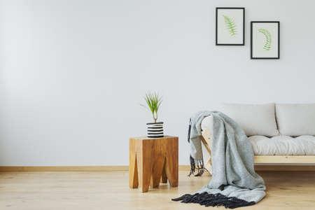 木製のスツールとスカンジナビアの家でデザイナーのソファ