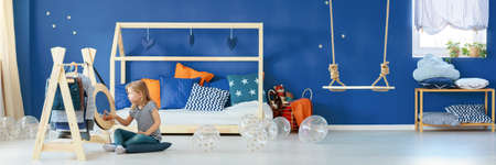 navy blue background: Little girl playing in her room with navy blue wall