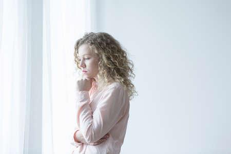 Jonge depressieve vrouw die naast het raam staat