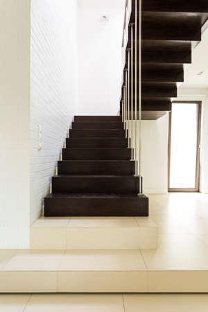 흰색과 밝은 집 복도에 어두운 최소한의 나무 계단