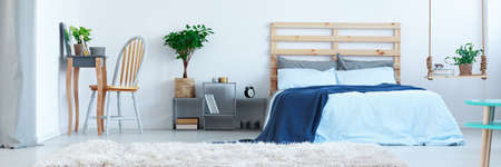 Stylish designed blue bedroom with plants and wooden decoration