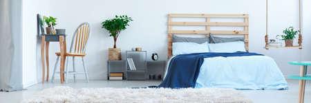 Stijlvol ontworpen blauwe slaapkamer met planten en houten decoratie