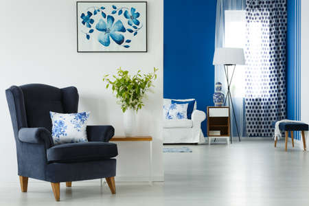 Blue armchair and vase with flowers in stylish living room