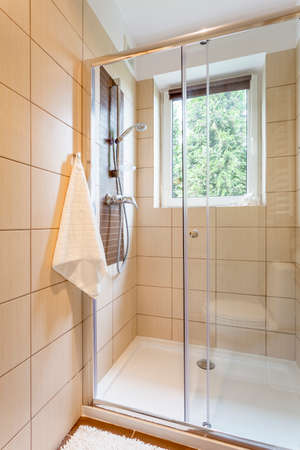 Bathroom with transparent shower stall and beige tiles