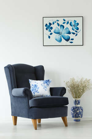 Armchair and porcelain vase with flowers against white wall with a poster
