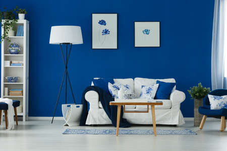 Stylish blue and white living room with sofa, table and lamp