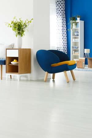 Blauwe stoel in ruime witte woonkamer