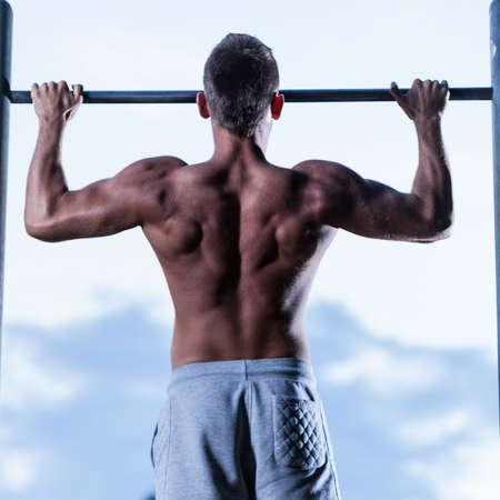 Sportman die op staaf in een parkgymnastiek bengelt Stockfoto