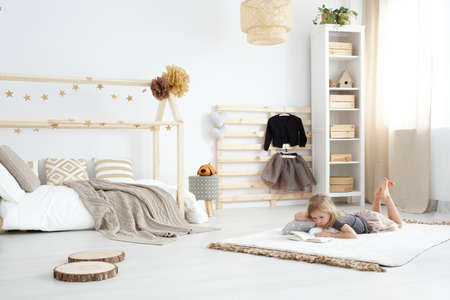 Girl playing in white spacious dreamy bedroom in scandinavian style