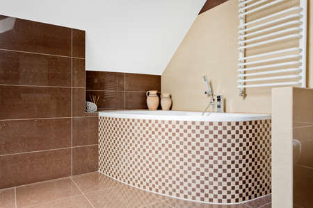 Modern and spacious bathroom with beige tiles in the attic