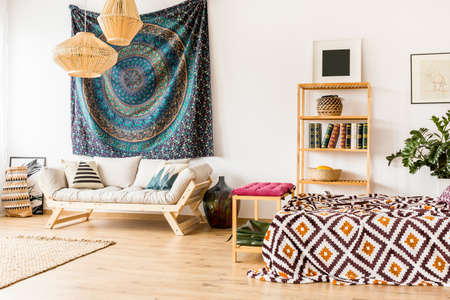 oriental rug: Ethnic accessories in modern room interior with bed and sofa
