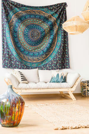oriental rug: Material on the wall, vase and sofa in ethnic living room Stock Photo
