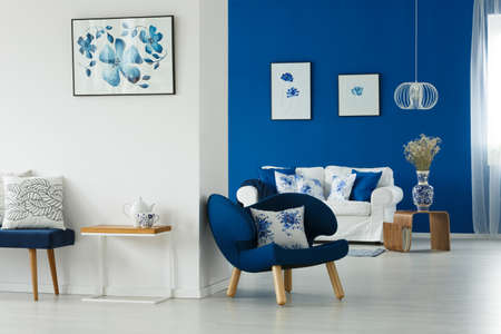 Cozy blue and white living room with flowery patterns on pillows and posters Banco de Imagens