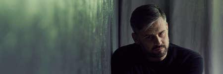 Glum man coping with depression, sitting in dark interior, panorama