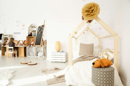 Scandinavian girls room decor in white color with wooden accessories