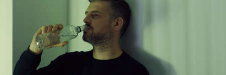 Drinker with bottle of vodka standing against wall, panorama