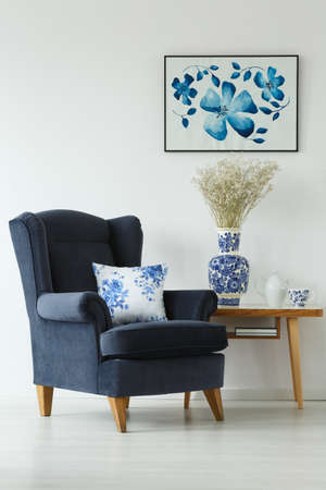 Armchair, wooden coffee table and flowery accessories in white room