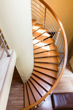 Wooden spiral staircase with minimalist railing in bright interior Imagens