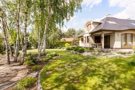 木と緑豊かな庭園とエレガントなモダンな戸建住宅 写真素材