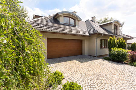 Detached family house exterior with cobblestone driveway to the garage and spruce garden