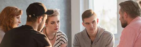 Psicoterapeuta che parla con adolescenti difficili durante la sessione di gruppo Archivio Fotografico - 81931417