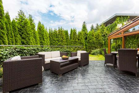 Groot terras terras met rotan tuinmeubelset omgeven door weelderig groen Stockfoto