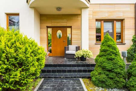 Entrada frontal elegante para a casa da família moderna, com abetos próximos ao caminho de paralelepípedos