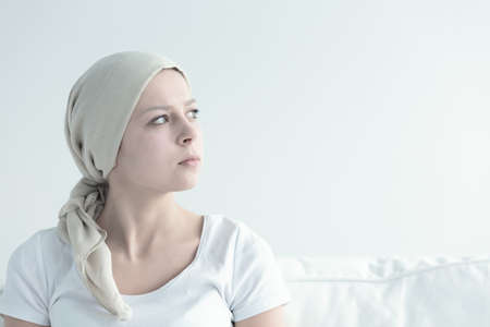 Woman after chemotherapy covering her head with white shawl