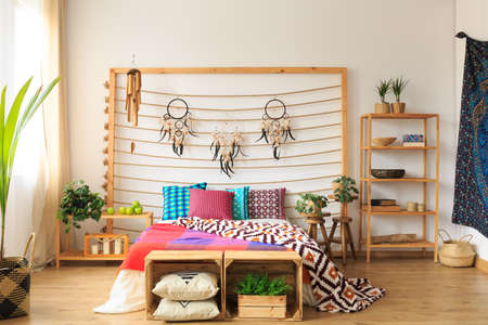Ethnic spacious colorful bedroom with wooden furniture