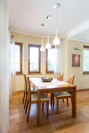 Comedor acogedor con mesa y sillas de madera clásicas en un interior moderno y luminoso Foto de archivo