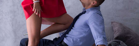 Cropped shot of a woman putting her knee on her lover's chest during foreplay