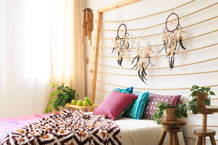 Bed with colorful blanket and pillows under bedheads with dreamcatchers Stock fotó
