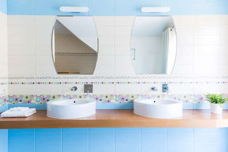 Two oval sinks with mirrors in the minimalist bathroom with blue tiles 版權商用圖片