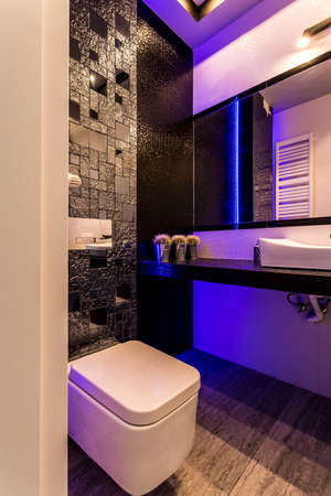 Stylish toilet with dark glossy wall, mirror and violet back light Stock Photo