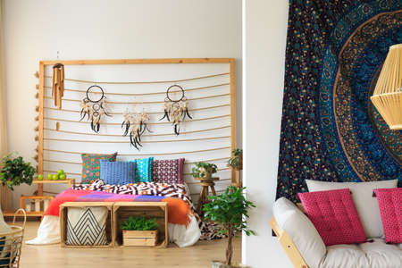 Three dreamcatchers hanging above the bed on rope
