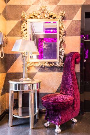 光沢のあるサイド テーブル ランプ、ユニークな音部記号アームチェア、beaufitul ミラー、壁に掛かっています。