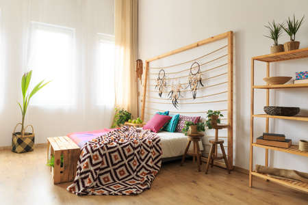 Colorful blanket falling from the wooden bed