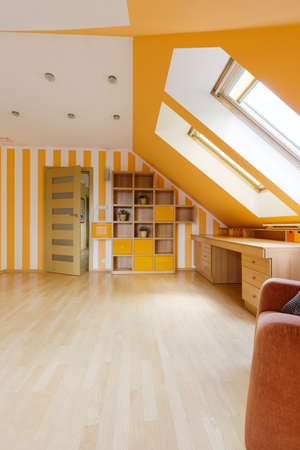 Attic decorated in sunny colors with wooden desk, bookcase and windows