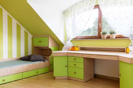Lichte kalkkamer voor tieners op de zolder met houten bed, bureau en raam