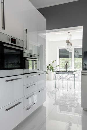 高光沢と白でモダンに整えられた清潔なキッチン