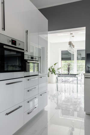 Modernly equipped clean kitchen in white with high gloss Archivio Fotografico