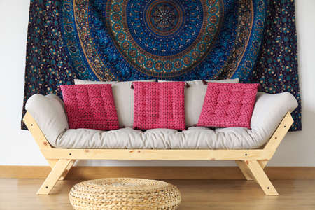 Wooden sofa with pink pillows standing in the room