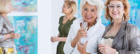 Female senior elegant friends celebrating at art exhibition